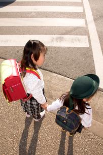 横断歩道の前で手を繋ぐ姉と妹の写真素材 [FYI03947998]