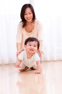 はいはいをする赤ちゃんと見守る母親の写真素材 [FYI03948152]