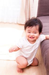 ソファーにつかまって立つ赤ちゃんの写真素材 [FYI03948164]