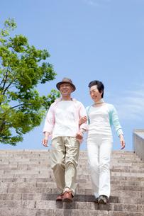 公園の階段を降りるシニア夫婦の写真素材 [FYI03948189]