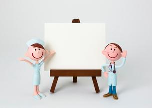イーゼルのホワイトボードの脇に立つ医師と看護師の写真素材 [FYI03948254]