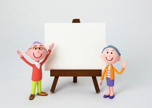 イーゼルのホワイトボードの脇に立つおじいちゃんおばあちゃんの写真素材 [FYI03948257]