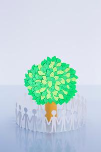 木を囲んで手をつなぐ人たちの写真素材 [FYI03948270]