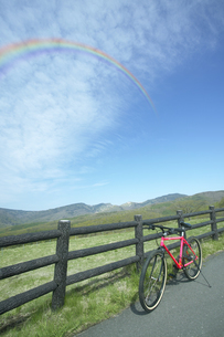牧場脇に自転車と虹の写真素材 [FYI03949438]