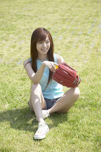 芝生に座るグラブとボールを持った女性の写真素材 [FYI03949822]