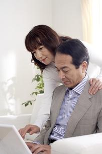 ソファーでパソコン画面を見る夫婦の写真素材 [FYI03949865]