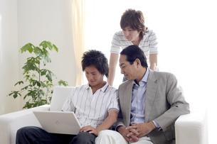 ソファーでパソコンを扱う親子の写真素材 [FYI03949869]