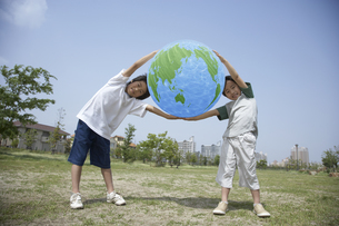 公園で地球のバルーンを持つ男の子2人の写真素材 [FYI03949940]