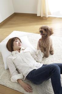 ラグに寝そべる女性と犬の写真素材 [FYI03949977]