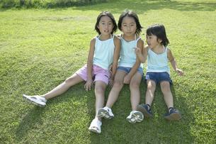 芝生に座る三姉妹の写真素材 [FYI03950066]