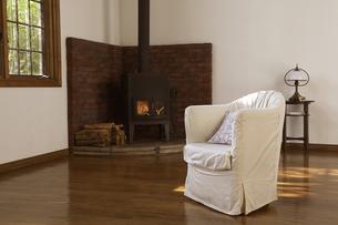 白いソファーとまきストーブの燃える部屋の写真素材 [FYI03950069]