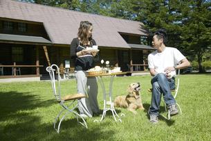 芝生でティータイムを楽しむカップルと犬の写真素材 [FYI03950079]