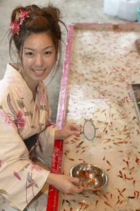 金魚すくいをする浴衣の女性の写真素材 [FYI03950141]