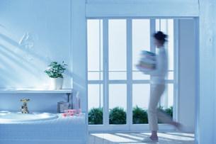 窓際を歩く女性の写真素材 [FYI03951682]