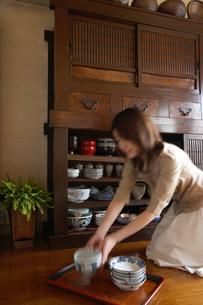 食器棚と女性の写真素材 [FYI03951779]