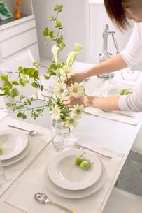 テーブルに花を生ける女性の写真素材 [FYI03951848]