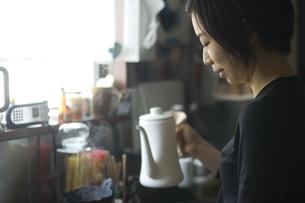 台所でポットを持つ女性の写真素材 [FYI03952587]