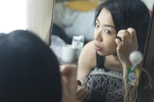 鏡を見て髪を直す女性の写真素材 [FYI03952588]