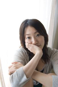 窓際に座る女性のポートレートの写真素材 [FYI03952607]