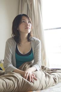 布団に座って上を見る女性の写真素材 [FYI03952609]