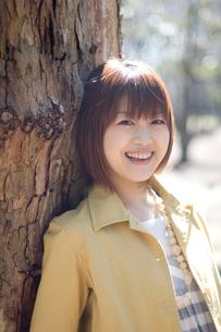 木にもたれる女性のポートレートの写真素材 [FYI03952616]