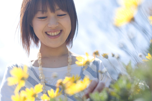 花を見て微笑む女性の写真素材 [FYI03952620]