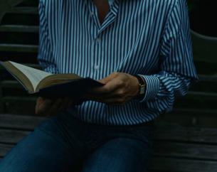 ベンチで読書している外国人男性の写真素材 [FYI03952655]