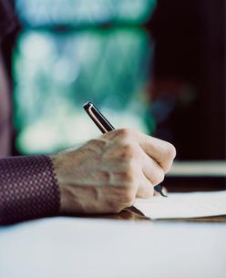 書斎で手紙を書く外国人男性の手の写真素材 [FYI03952657]