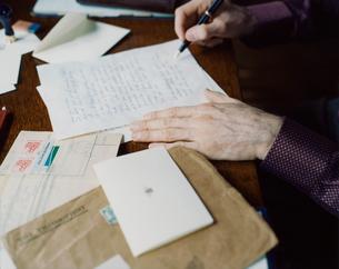 書斎で手紙を書く外国人男性の手の写真素材 [FYI03952662]
