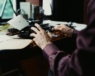 書斎でタイプライターを打つ外国人男性の手の写真素材 [FYI03952664]