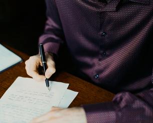 書斎で手紙を書く外国人男性の手の写真素材 [FYI03952666]