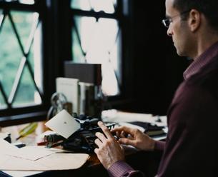 書斎でタイプライターを打つ外国人男性の写真素材 [FYI03952667]