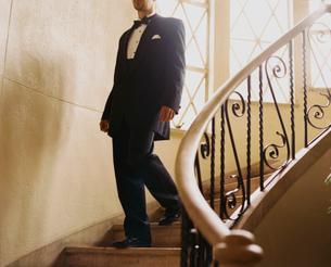 階段を下りるタキシード姿の外国人男性の写真素材 [FYI03952670]
