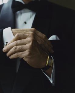 タキシード姿の外国人男性がカフスを直す手の写真素材 [FYI03952674]
