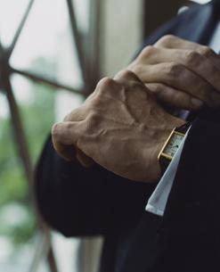 タキシード姿の外国人男性がカフスを直す手の写真素材 [FYI03952677]
