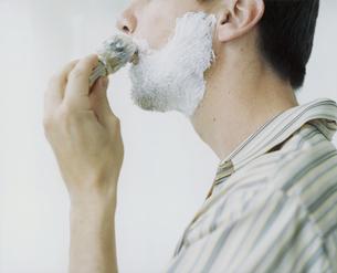 鏡に向かいシェービングする外国人男性の写真素材 [FYI03952685]