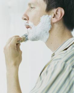 鏡に向かいシェービングする外国人男性の写真素材 [FYI03952687]