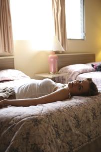 モーテルのベッドに横たわる女性の写真素材 [FYI03952724]