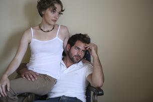 椅子に座って寄り添う男性と女性の写真素材 [FYI03952728]