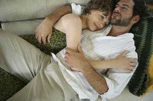 ソファーの上で密接に体を寄せ合う男性と女性の写真素材 [FYI03952746]