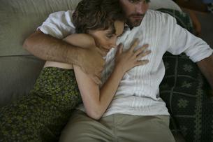 ソファーの上で密接に体を寄せ合う男性と女性の写真素材 [FYI03952747]