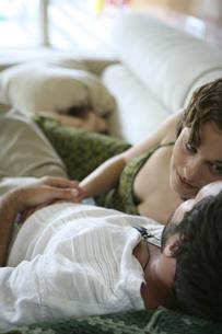 ソファーの上で密接に体を寄せ合う男性と女性の写真素材 [FYI03952750]