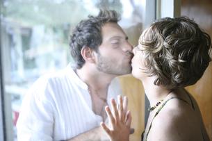 ガラス越しにキスをする男性と女性の写真素材 [FYI03952763]