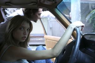 運転席に座る女性とドアを開ける男性の写真素材 [FYI03952781]