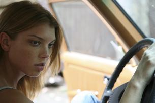 運転席に座りハンドルを握る女性の写真素材 [FYI03952785]