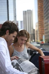 路上で新聞を読む男性と女性の写真素材 [FYI03952792]