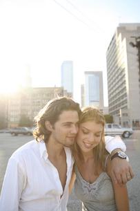 街中で肩を寄せ合う男性と女性の写真素材 [FYI03952801]