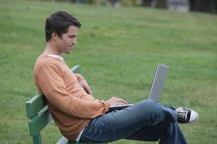 公園のベンチに座ってパソコンをする男性の写真素材 [FYI03952811]