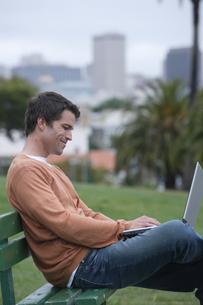 公園のベンチに座ってパソコンをする男性の写真素材 [FYI03952812]