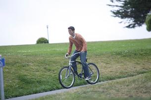 自転車で公園を走る男性の写真素材 [FYI03952813]